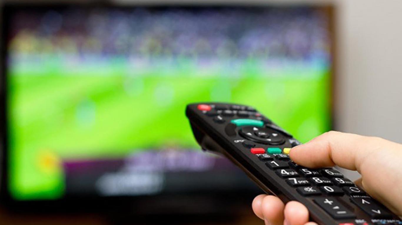 mando a distancia en mano con television con fútbol